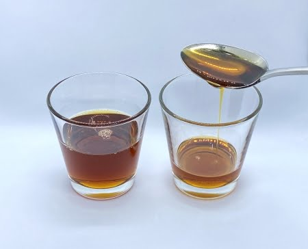 Two glasses Pure Maple Syrup Dark Robust, maple syrup pouring from spoon into right hand glass. Dark clear clarify of maple syrup.