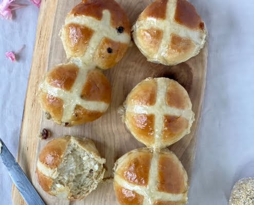 Maple Hot Cross Buns on a wooden board with a piece torn off one bun and butter spread on it - Pure Maple