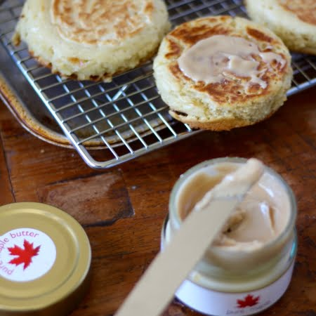freshly cooked crumpets, jar of maple butter spread over top of crumpet