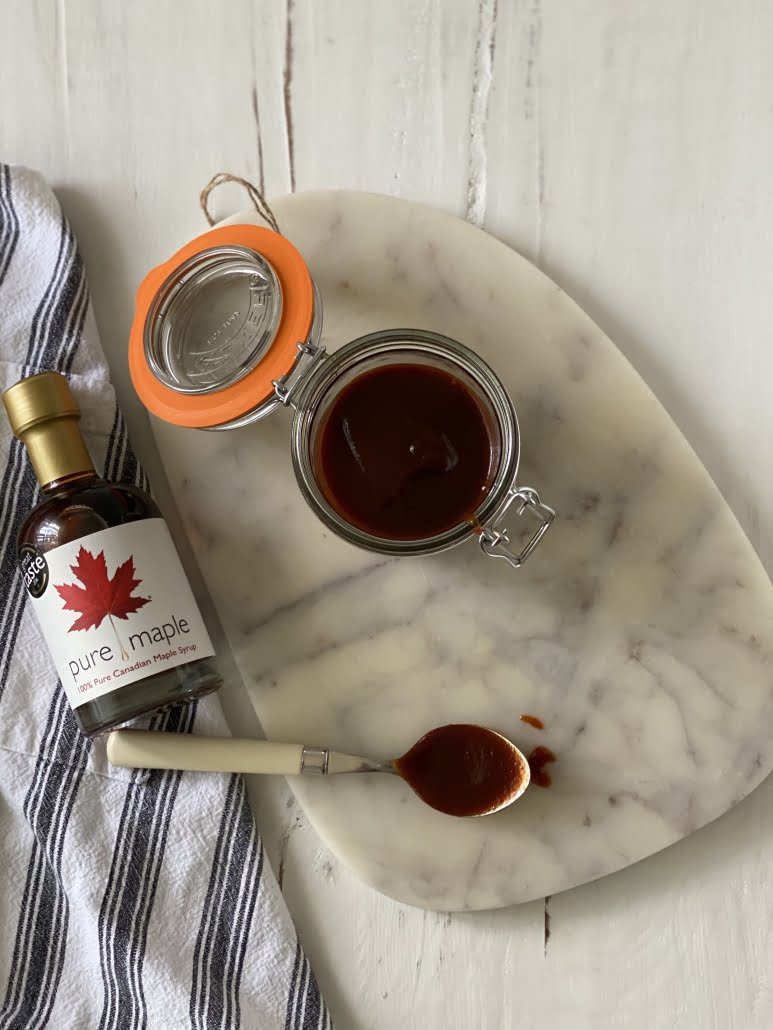pot of prepared Maple Barbecue Sauce next to bottle of maple syrup, spoon on table covered in sauce