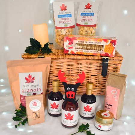 Maple Lovers Christmas Hamper basket surrounded by maple syrup food products including decorative Christmoose on top of bottle