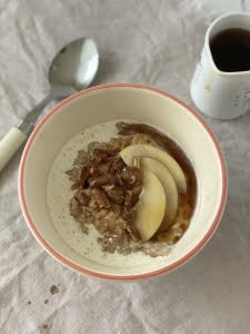 Spiced apple porridge with apple slices, pecans, cream and maple syrup