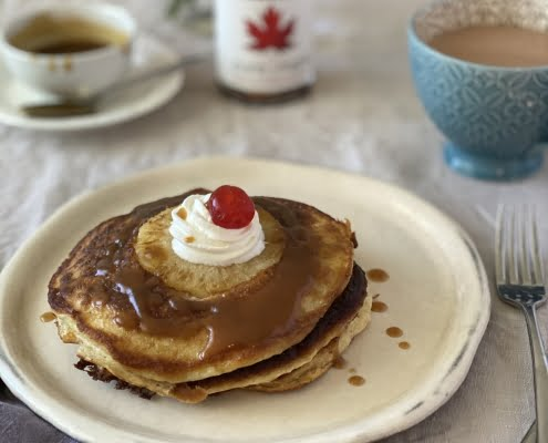 Upside down pineapple pancakes with maple caramel sauce, whipping cream and a cherry on top - Pure Maple Syrup