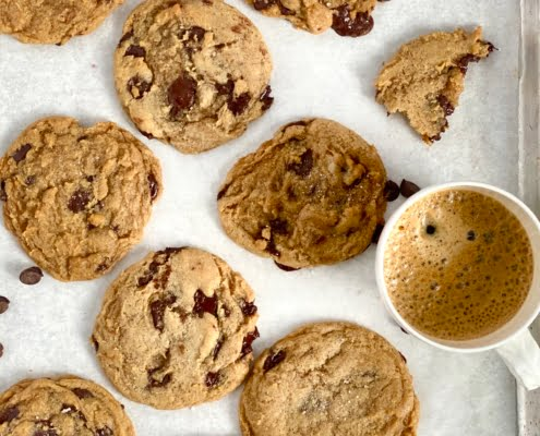 Vegan Chocolate Chip Cookies on a baking tray with a cup of coffee - Pure Maple