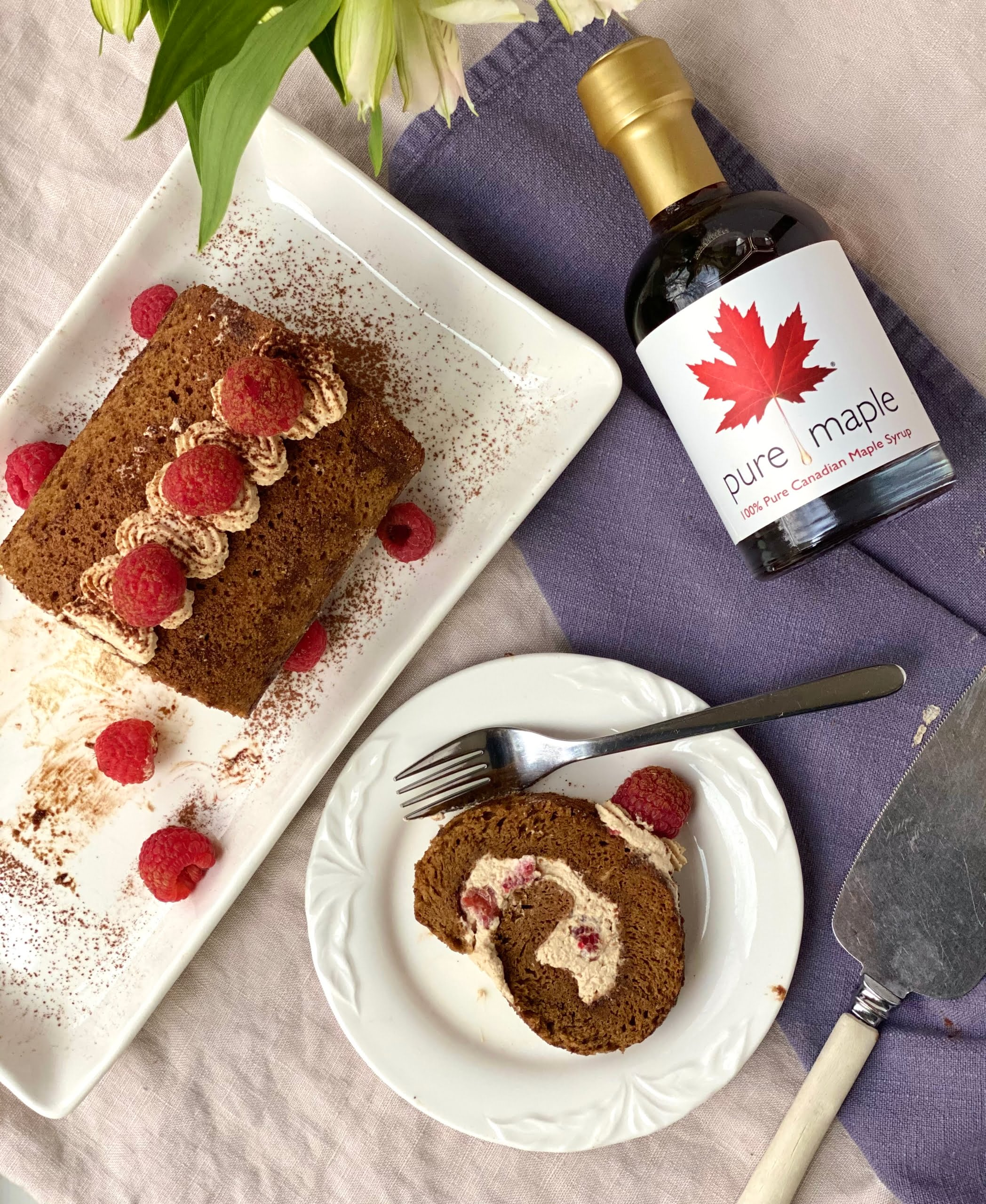 Maple Espresso Roll with Raspberries showing a slice cut and maple syrup bottle - Pure Maple