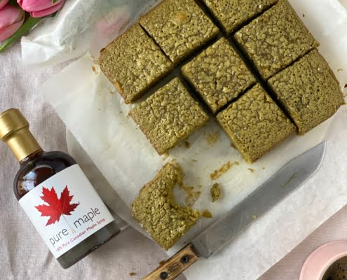 Salted Matcha Brownies with a bite taken from one and maple syrup bottle to the left - Pure Maple