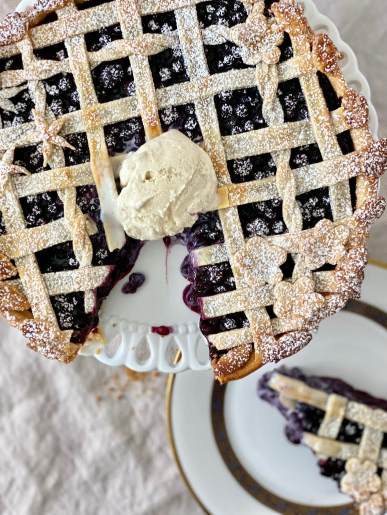 Blueberry pie dusted with icing sugar and served with a scoop of vanilla ice cream with a piece of pie cut out and served on a plate - Pure Maple