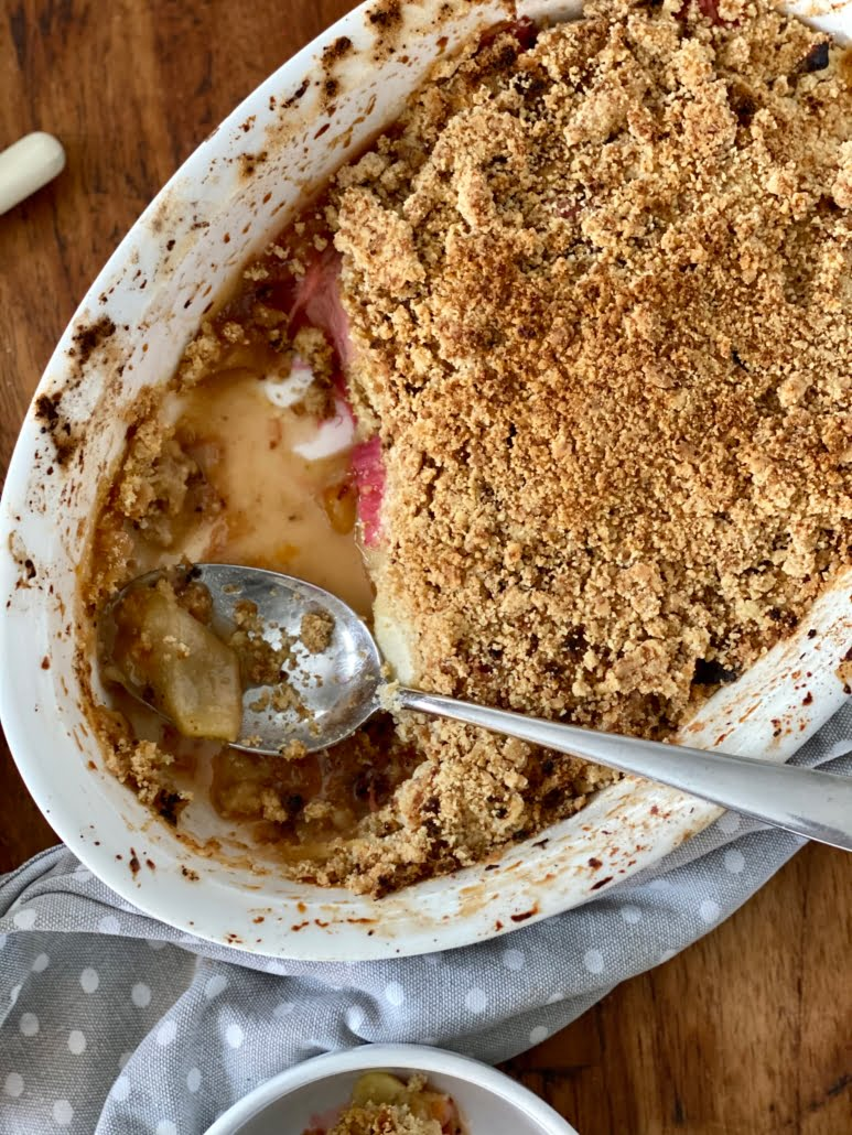 Maple rhubarb and apple crumble in an oval shallow baking dish with a couple servings removed and a large spoon to the side - Pure Maple