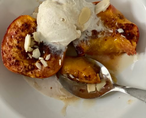Maple Baked Peaches with a scoop of vanilla ice cream, flaked almonds and maple syrup with a small bit cut off - Pure Maple