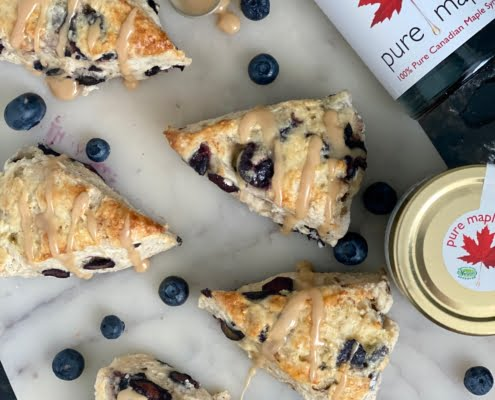 Maple Blueberry Scones drizzled with maple and a maple syrup bottle and maple butter jar on one 1 side