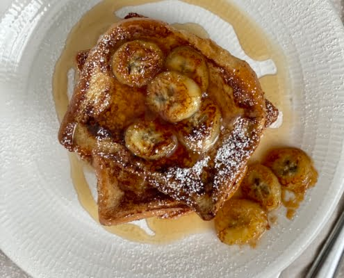 French Toast with Maple Caramelized Bananas on the top and 3 arranged on the side of the plate with a dusting of icing sugar and drizzled with maple syrup -Pure Maple