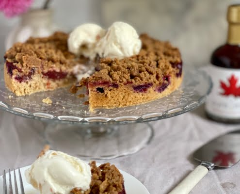Plum cake with streusel topping and vanilla ice cream with a piece cut out - Pure Maple