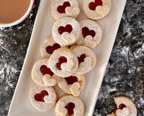 Maple Jammy Biscuits on a plate with a cup of tea and 1 biscuit on the side with a bite taken